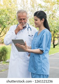 Senior doctor in lab coat with a stethoscope and young nurse discussing over digital tablet in garden at hospital. Medicine, health care and technology concept