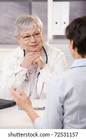 Senior doctor listening to patient in office, smiling.?