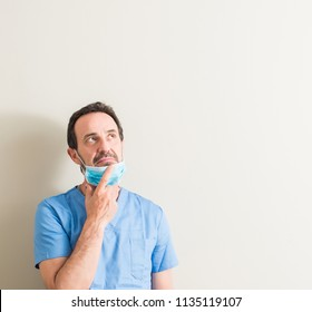 Senior doctor man using mask serious face thinking about question, very confused idea