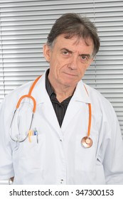 Senior doctor on grey background looking at the camera