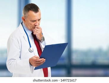 Senior doctor reading a case history