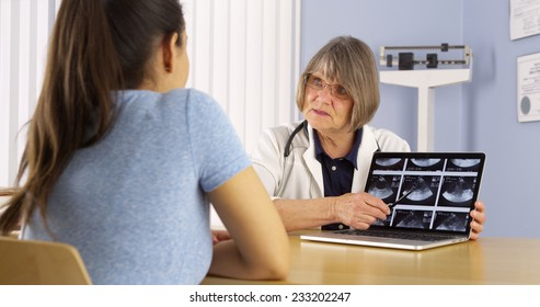 Senior doctor reviewing Mexican woman's pregnancy scans