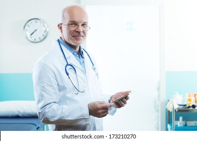 Senior doctor with tablet and medical equipment in the background.