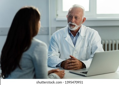 Senior doctor talking to female patient during medical consultations at doctor's office.