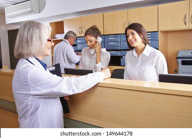 Senior doctor talking with receptionist at hospital reception