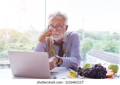 Senior doctor using laptop computer in office. Nutritionist thinking idea in chemical formula for medicine nutrition.