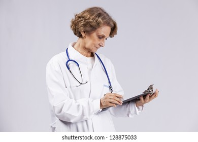 Senior doctor writing on the notepad(isolated on gray)