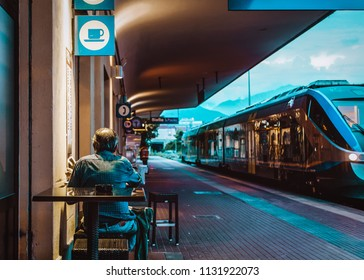 Senior drinks coffee and quietly reads newspaper on train station bar, Stazione San Paolo, Biella, Italy in 4 July, 2018.