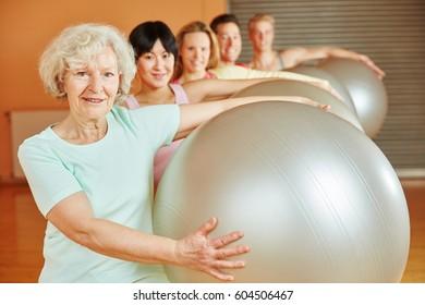 Senior during ball exercise in pilates at fitness studio