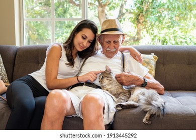 Senior eighty plus year old man with granddaughter in a home setting petting a cat.