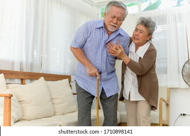 Senior elder Asian man has a severe heart attack symptom in his house living room and been take care by his wife suddenly. Senior health or health care concept.