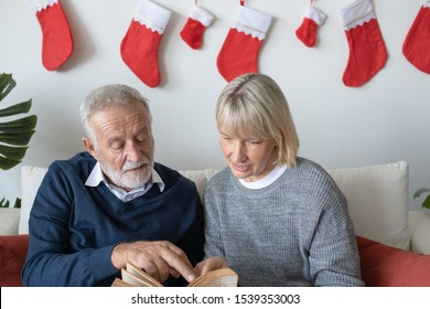 senior elderly caucasian old man and woman reading book and sitting on sofa to discussion together in living room that decorated for christmas festival day in the morning, retirement family concep