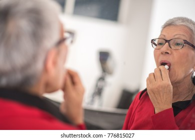 Senior elderly lady applying red lipstick, doing her daily make-up routine