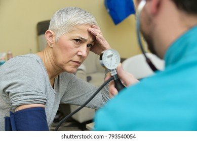 Senior elderly lady receiving bad news about her blood pressure from her doctor or a nurse