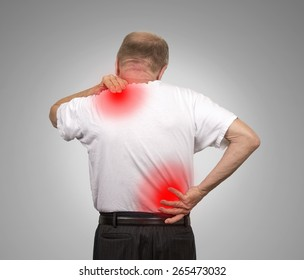 Senior elderly man with lower and upper back pain isolated on gray wall background. Spinal cord problems