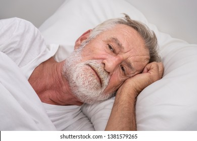 Senior elderly man on bed eye open sleeplessness and worry, with white blanket in bedroom