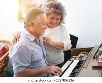 Senior elderly man plays piano in nursing home listened to by elderly woman,Retreatment elderly asian grandmother and grandfather play piano in home with love moment.