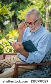 Senior elderly man reading book with mug of coffee in garden putting on glasses