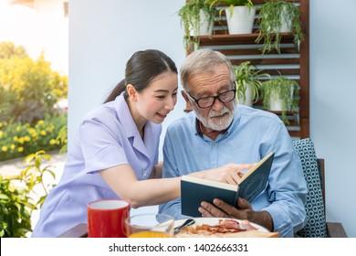 Senior elderly man reading book with nurse during breakfast in garden at nursing home