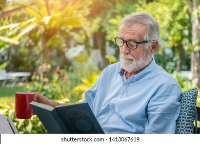 Senior elderly man reading book drinking mug of coffee in garden