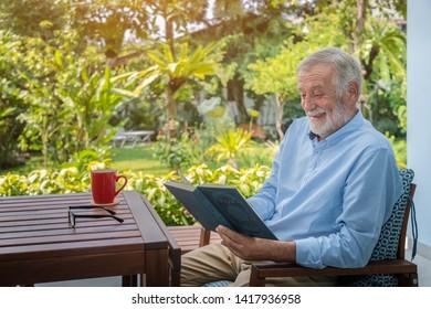 Senior elderly man reading book with mug of coffee in garden