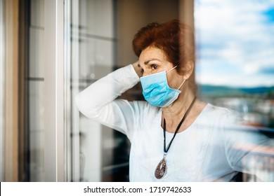 Senior elderly sad woman at home looking through the window.Coronavirus COVID-19 disease outbreak infection risk.Lockdown socialization restriction activity.Quarantine mental health effect - Shutterstock ID 1719742633