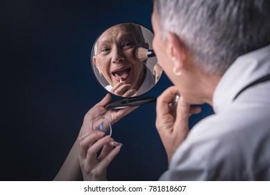 Senior elderly woman applying make up, looking herself at a hand mirror