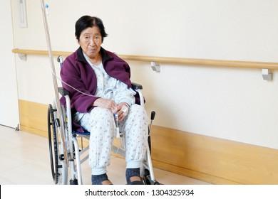 senior or elderly woman patient on wheelchair so sad in hospital hallway