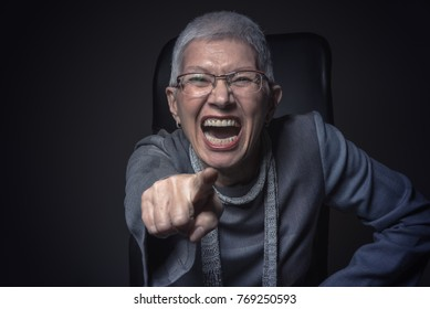 Senior elderly woman pointing finger, screaming with rage, placing the blame on you