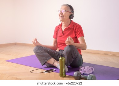 Senior elderly woman practicing meditation, yoga or pilates, listening to her favorite music