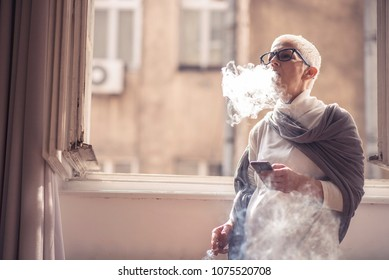 Senior elderly woman smoking a cigarette next to a big window in her house
