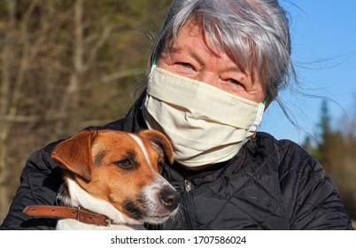 Senior elderly woman wearing white cotton home made virus mask her dog on hands. Life during coronavirus covid-19 outbreak illustration