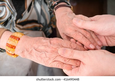 Senior or eldery assistance concept. Young man holds hands of senior woman.