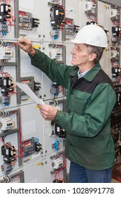 Senior electrician with a screwdriver and wiring diagram in his hand standing near an an electric shield
