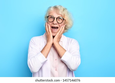 senior emotional doctor woman terrified with fear, shouting in shock. Panic concept.woman in glasses with wide open mouth expresses fear, surprise. isolated blue background. studio shot.