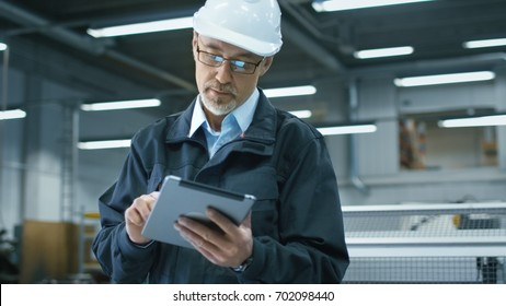 Senior engineer in hardhat is using a tablet computer in a factory.