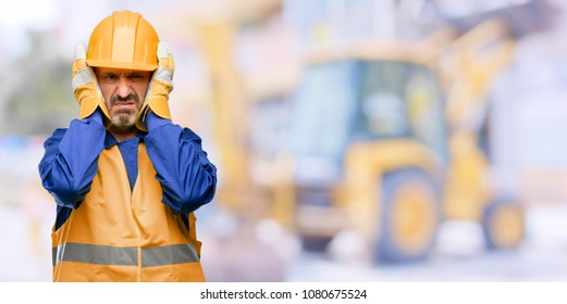 Senior engineer man, construction worker covering ears ignoring annoying loud noise, plugs ears to avoid hearing sound. Noisy music is a problem. at work