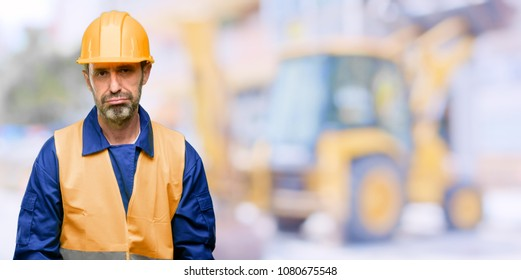 Senior engineer man, construction worker with sleepy expression, being overworked and tired at work