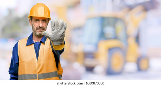 Senior engineer man, construction worker annoyed with bad attitude making stop sign with hand, saying no, expressing security, defense or restriction, maybe pushing at work
