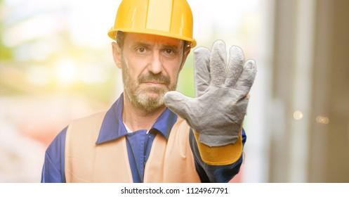 Senior engineer man, construction worker annoyed with bad attitude making stop sign with hand, saying no, expressing security, defense or restriction, maybe pushing