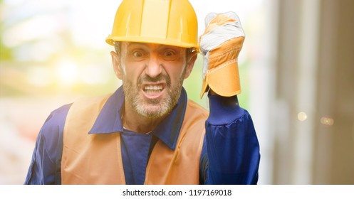 Senior engineer man, construction worker irritated and angry expressing negative emotion, annoyed with someone