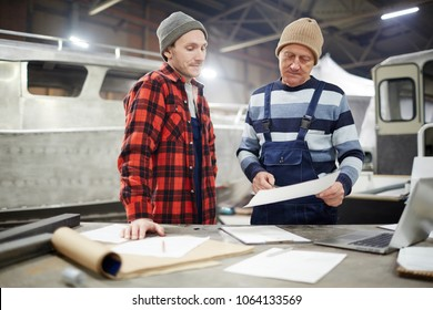 Senior engineer pointing at paper with sketch of new boat while explaining it to young colleague