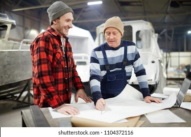 Senior engineer showing his shipbuilding sketch to young colleague and explaining it