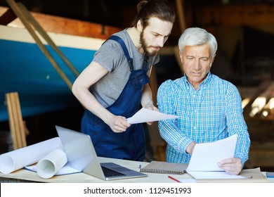 Senior engineer showing important information in document to his trainee at meeting