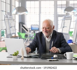 Senior engineer sitting at desk doing design work with computer at architect studio.