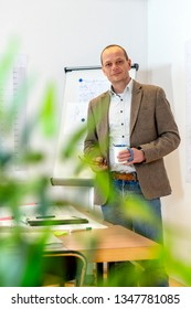 Senior engineer standing next to a desk, littered with technical drawings, pens, markers and notepads, in front of a magnetic white board with drawings on it, seen throug the leaves of a plant