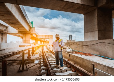 A senior engineer under inspection and checking construction process railway and checking work on railroad station platform .Engineer wearing safety uniform and safety helmet in work.