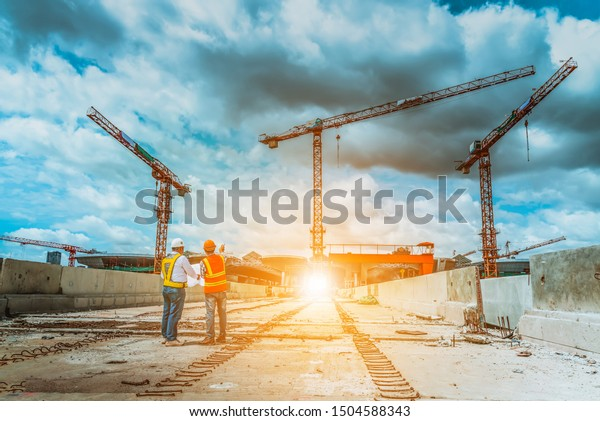 A senior engineer under inspection and checking construction process railway and checking work on railroad station with blueprint .Engineer wearing safety uniform and safety helmet in work.