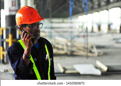 Senior engineer using walkie-talkie at warehouse construction site.