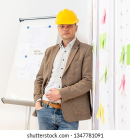 A senior engineer, wearing a hard hat leaning against a wall with several planning boards and sticky notes attached to it.
